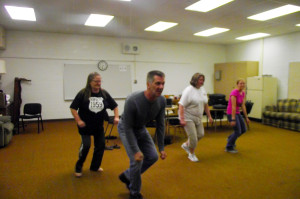 During the early days of the Virgin Valley Theatre Group's workshop the actors/dancers learned the choreography for Fly Willie in room 15, the Green Room for the Mesquite Community Theatre. Here workshop participants Patty Amore, Jennifer Conklin and Emily Conklin follow Fly Willie Writer/Choreographer Dan Nielsen while he shows the group choreography for a simple dance scene. Photo by Teri Nehrenz