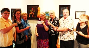 An excited Diana Coonradt, center, is surrounded by Eureka employees as she shows off her painting, Vincent's Song, that captured their Sponsor's Choice ribbon.