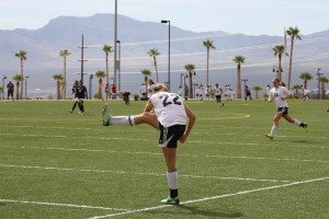 Bulldog striker Abbie Barnum #22 finishes off a long shot on goal Saturday morning against Canyon Springs. Barnum would strike goal five times during the Mesquite Cup. Photo by Lou Martin.
