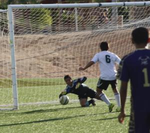 Bulldog goalkeeper Domingo Ramirez dives for a save in the first half against Sunrise Mountain as teammate Oswaldo Cabrera comes in for support. Ramirez had 8 saves in the first half. Photo by Lou Martin.