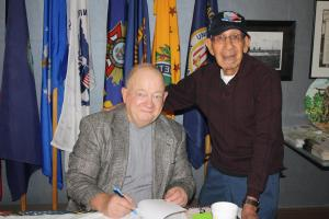 Author Jim Carrick autographs his book for 93 year old Veteran of WW11 Eddie Gutierrez Saturday morning at the Vet Center. Photo by Lou Martin