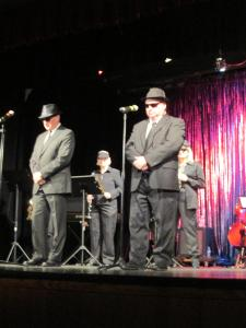 John Dearing, left, and Brian Wursten, right, closed out the night with their rendition of the Blues Brothers, accompanied by the 12-piece Mesquite Community Band in sunglasses. Photo by Stephanie Frehner.