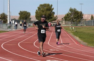 Participants circle the track in the Race Walk competition. Photo by Burton Weast