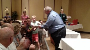 VVHS Football Coach Yori Ludvigson hands over a sweet prize to a lucky boy who happened to be sitting on the right number at Saturday's Desserts in the Desert event at the Eureka Casino, benefiting Icing Smiles Charity. Photo by Stephanie Frehner.