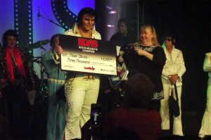 Tyler James not only took home the prizes for the 60's and 70's eras, he also took home the title of overall winner of the 2015 Elvis Rocks Mesquite Competition held June 18-20 in the CasaBlanca Showroom.  Krissy Ayon, Entertainment Director for the CasaBlanca Resort, presents James with his trophy and a check for $3,000. Photo by Teri Nehrenz.