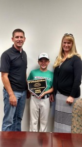 Kurt Felix, middle, stands with his dad, Jon, and mom, Amy, with his award he received for taking first place in his division when competing in San Diego. Photo by Stephanie Frehner.