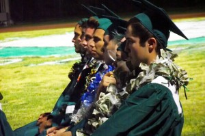 Virgin Valley High School graduating seniors wear a variety of adornments from awards earned for excellence to money and candy necklaces from supporters and well-wishers.  These graduating seniors listen intently as their principal address the class of 2015, their families and friends during the commencement ceremony held on June 4, 2015. Photo by Teri Nehrenz.