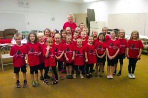 """Approximately half of the littlest Mesquite Kids On Stage are in the production """"Broadway Beat"""" and on stage for the first time ever in their lives.  This brave and promising group of thespians, singers and dancers absolutely were a hit and won over the hearts of the audience opening night July 1, 2015.  The kids took a minute to pose for the picture before they had to rush back on stage.   Dance coach, Donna Eads, stands behind her young dancers filled with pride just for a minute before ushering them out of the Green Room and onto the stage for their next number. Photo by Teri Nehrenz"""