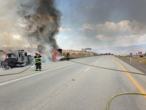 Mesquite Fire Rescue and other crews work to extinguish the fire at the scene Sunday. The flames from the semi truck had spread to shrubs around it, but was restricted to an eighth of an acre in size. Photo courtesy of Mesquite Fire Rescue.
