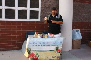 Mesquite Sports and Leisure Director Nick Montoya, also the Bulldog freshman coach points out food items collected earlier in the evening for the Virgin valley Food Bank. Photo by Lou Martin