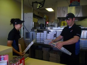 Business partners Jodi Garner, left, and Doug Reed have just purchased Dominos Pizza located at 360 N. Sandhill Blvd. Garner and Reed are preparing for their daily business demands by folding pizza boxes, one of the many tasks necessary to open the store at 10:30 a.m. Photo by Teri Nehrenz.