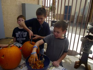 "Asher, Hyrum and Ezra Baker scoop out the ""awesome feeling"" pumpkin seeds and mess so their mom can begin carving out the perfectly scary Jack-0-Lantern this family plans on showing off on their front porch.  The Bakers are just one of the many families who attended the Virgin Valley Heritage Museum's free-to-the-public Pumpkin Carving and Painting event on Oct. 17.  Photo by Teri Nehrenz."