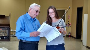 """Orchestra Conductor and Symphony Organizer Selmer Spitzer reviews some of the material for the upcoming """"A Musical Thanksgiving"""" program on Nov. 14. Photo by Stephanie Frehner."""