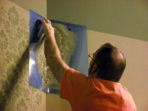 Glen Bjornson, Virgin Valley Theatre Group Artistic Director and Set Designer of the VVTG's season opener Angel Street, painstakingly applies stenciling to the many walls in the Old English, Victorian style living areas to mimic wallpaper. Photo by Teri Nehrenz