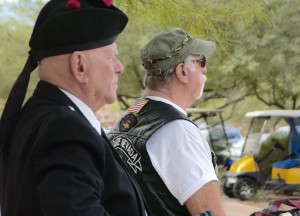 Bagpiper Dennis Hangey and Mayor Litman watch flag raising. Photo by Burton Weast.