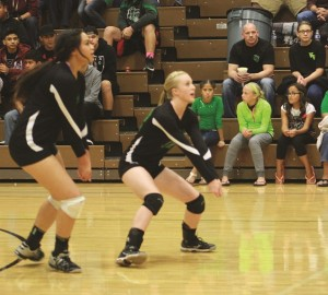 Bulldogs Bernice Fiso left and Emma Barnum right prepare to receive a Trojan serve Tuesday night during the dawgs 3-0 win over Pahrump Valley. Photo by Lou Martin.