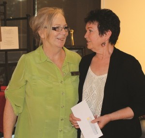 """Jan Hansen, right, receives a cash award from Jean Wiensch, President of Virgin Valley Artists Association, for her blue ribbon watercolor, """"Fanciful View,"""" in the October Flight of Fancy art exhibition at the Mesquite Fine Arts Gallery. Photo by Barbara Ellestad."""