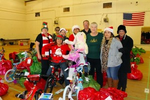 Roberta Franco (center) and her army of volunteers distributed hundreds of toys and clothing articles to families for the Angel Tree Project on Dec. 18. Photo by Teri Nehrenz.
