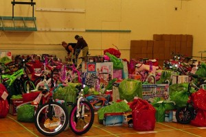 """The floor in the old Boxing Club was filled with colorful packages containing toys and clothing for 116 families and 256 children who live in and around Mesquite. Volunteers said, """"Mesquite residents were extremely generous this year with donations that will make hundreds of Mesquite children very happy this Christmas"""". Photo by Teri Nehrenz."""
