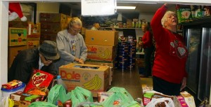 Volunteers at the Beaver Dam Food Bank get ready to open their doors to serve 65 families that receive their assistance on a weekly basis.  Money from the recent Beaver Dam Mafia fundraising golf tournament helped to purchase hams for the families' Christmas dinners.   Photo by Teri Nehrenz.