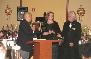 Keith Buchhalter, left presents an appreciation award to outgoing Chamber Board President Ken Cook, right as Director of Chamber Administration Brenda Snell looks on. The award was presented at the Mesquite Chamber of Commerce Black and White Holiday Gala, Dec. 5 held at the Eureka Casino Resort. Photo by Burton Weast.