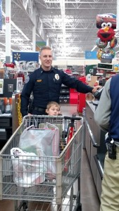 Lieutenant MaQuade Chesley took a break from his duties to help out with the Shop With A Cop program, pictured here with Taylor. Photo by Stephanie Frehner.