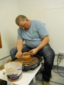 Clint Mecham hard at work at the potter wheel. Photo by Linda Faas.