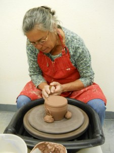 Karen Miskimins shapes a jar as she learns how to use the potters wheel. Photo by Linda Faas.