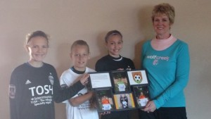 From left, Jaymie Hulet, Zachary Trimming and Addison Pletzke present a thank-you plaque to Kathy Bussman, treasurer.  In the plaque, the athletes pledge to work hard in their sport and to be an example for others to follow.