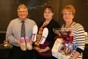 """Jeffrey Bird, left, Lauren Deihl, and Roberta Bird, all of Financial Concepts, hold the winner's statute for their entry in the Virgin Valley Artists Association contest """"These Shoes weren't meant for walking"""" that raised $755 for student scholarships. Photo by Barbara Ellestad."""
