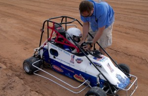 "Jeff Hobbs straps his son ""Ace"" Hobbs into the quarter midget race car. Photo by Burton Weast."