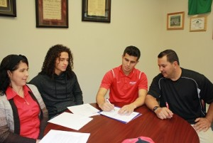 Bulldog soccer star Moises Medina signs his scholarship offer from Dixie State University in St. George, Utah Friday, Feb. 5 at Virgin Valley High School. From left are Medina's mother Raquel, brother Gabe, Moises and father Joel. Photo by Lou Martin.