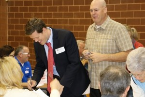 RepublicanCaucus-02-23-16:  City Attorney Robert Sweetin, left and Mesquite Police Department Chief Troy Tanner sign in at the Mesquite Republican caucus site Tuesday, Feb. 23. Record numbers of voters turned out for this year's caucus. Photo by Barbara Ellestad.
