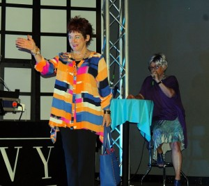 Ms. Senior Mesquite Fashion Show 2016 01:  Jean Watkins, Ms. Senior Mesquite Founder models a brilliantly colored ensemble from Bealls Department Store during the 2016 Ms. Senior Mesquite Fashion Show while Master of Ceremonies, Bunny Wiseman, describes the pieces to a packed house at Envy Night Club on Saturday, March 5. Photo by Teri Nehrenz.