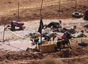 The mud crawl under barbed wire was just one of the mandatory obstacles Spartan Racers from around the U.S. had to overcome to complete the eight-mile course during the 'Super Spartan' races held at the Mesquite MX Park and Hafen Ranch on March 19. Photo by Teri Nehrenz.
