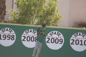 Surrounded by state championship banners Bulldog right fielder Jacob Ruvalcaba goes high near the wall to pull down a potential Cowboy home run Tuesday, April 19 during the Dawgs 5-0 loss.