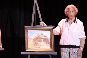 Second runner up to Ms. Senior Mesquite 2016, Elizabeth Merrill, showcases some of her wonderful paintings.  Merrill never took a lesson but rather just followed her desire when she was 43 and began painting.  She presented several of her works during the talent portion of the competition.  Photo by Teri Nehrenz.