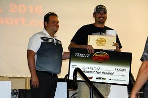 Mesquite Gaming's Christian Adderson presents Lucky's Q's head Cook Justin McGlaun with a check for $1,500 for taking first place in the chicken category.  Photo by Teri Nehrenz.
