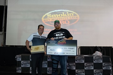 Clark Crew BBQ's Travis Clark didn't just take home the brisket; he also took home to Yukon, OK the bragging rights and the check for $14,000 along with the title of the Smokin in Mesquite 2016 Grand Champion.  Presenting the check is Mesquite Gaming's Christian Adderson.  Photo submitted.