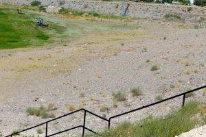 The barren hillside above the sports field at Beaver Dam Jr./Sr. High school erodes away during each rain spilling debris onto the field below.  Photo by Teri Nehrenz