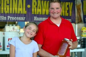 Joshua and Sarah Hammons offer sweet samples of their fresh, raw honey.  You can find them on Facebook and if you have a bee problem, give the Hammons a call; they also handle bee rescues.  Photo by Teri Nehrenz