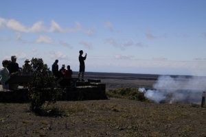 visitors take in the dramatic view of the volcanic crater in Volcano National Park, HI