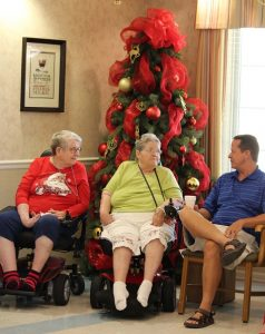 Family members were happy to help celebrate Christmas in July with their loved ones at Highland Manor on July 27.  Robert Noreen (right) visits with mom Barbara Noreen (middle) and her friend Ethel Hansen (left).  Photo by Teri Nehrenz