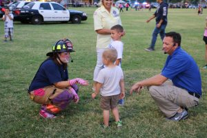 Firefighters AprilLee Lebaron, left, and Spencer Lewis, right, take some time in between skits to interact and talk with Mesquite's youth at the 2016 Mesquite Night Out event on Sept. 21. Photo by Stephanie Clark.