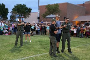 """Virgin Valley High School Senior Reid Jensen volunteered to be tazed at this year's Mesquite Night Out on Sept. 21. Jensen was talked into it by his brother-in-law Quinn Averett, who is currently the Public Information Officer with Mesquite Police Department. Jensen said he volunteered because """"I thought it would be real cool to do it,"""" he said. """"I couldn't really move."""" Thankfully, the effects of the paralyzing tazor wore off before his performance at the football game two days later where he plays as a tight end. After high school, Jensen will depart for a two-year mission. Averett told the MLN that the amount of power in this instance was about 10,000 watts. """"The stun mimics the central nervous system, and while the person cannot move or talk, they can still think and breathe. We usually only have to use extreme force like this two to three times per year, which considering the amount of arrests and incidents, is very low."""" Photo by Stephanie Clark."""