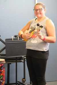 Emily Walsh demonstrates how to hold a Ukulele as she spends hours helping to tune the 30 new Ukuleles donated by Kala Music.  Photo by Teri Nehrenz