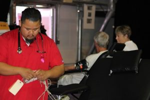Eric Paguia, Red Cross technician, processes bags for visitors who are about to donate blood during the Health and Wellness Fair held at the Casablanca Event Tent on Friday, Sept. 16. Photo by Teri Nehrenz