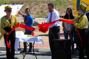 While Mesquite Showgirls hold it, Rotary 5300 District Governor Luciano de Sylva cuts the ribbon on the Beaver Dam Beautification Project during a dedication ceremony held on Sept. 15. Photo by Teri Nehrenz