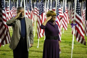 Deacon Gary Jacobs and Barbara Ellestad salute the American flag during the 2016 1000 Flags over Mesquite Veteran's Day ceremony. Photo by Teri Nehrenz