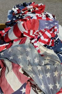 A pile of used and unserviceable U.S. flags lay ready for the fire during a ceremony led by Mesquite Fire Captain William Martinez. Photo by Barbara Ellestad.